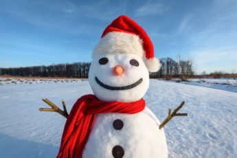 Funny snowman in Santa hat and red scalf on snowy field. Merry Christmass and happy New Year!